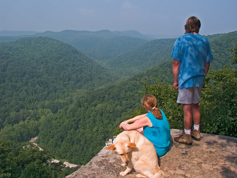 people sitting at an overlook at Pipestem State Park