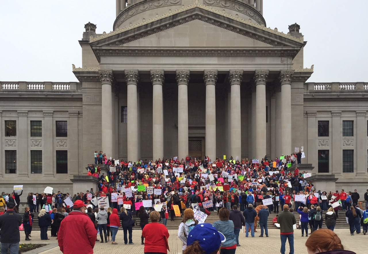 large group of teachers holding signs protesting on the steps of the WV state capitol