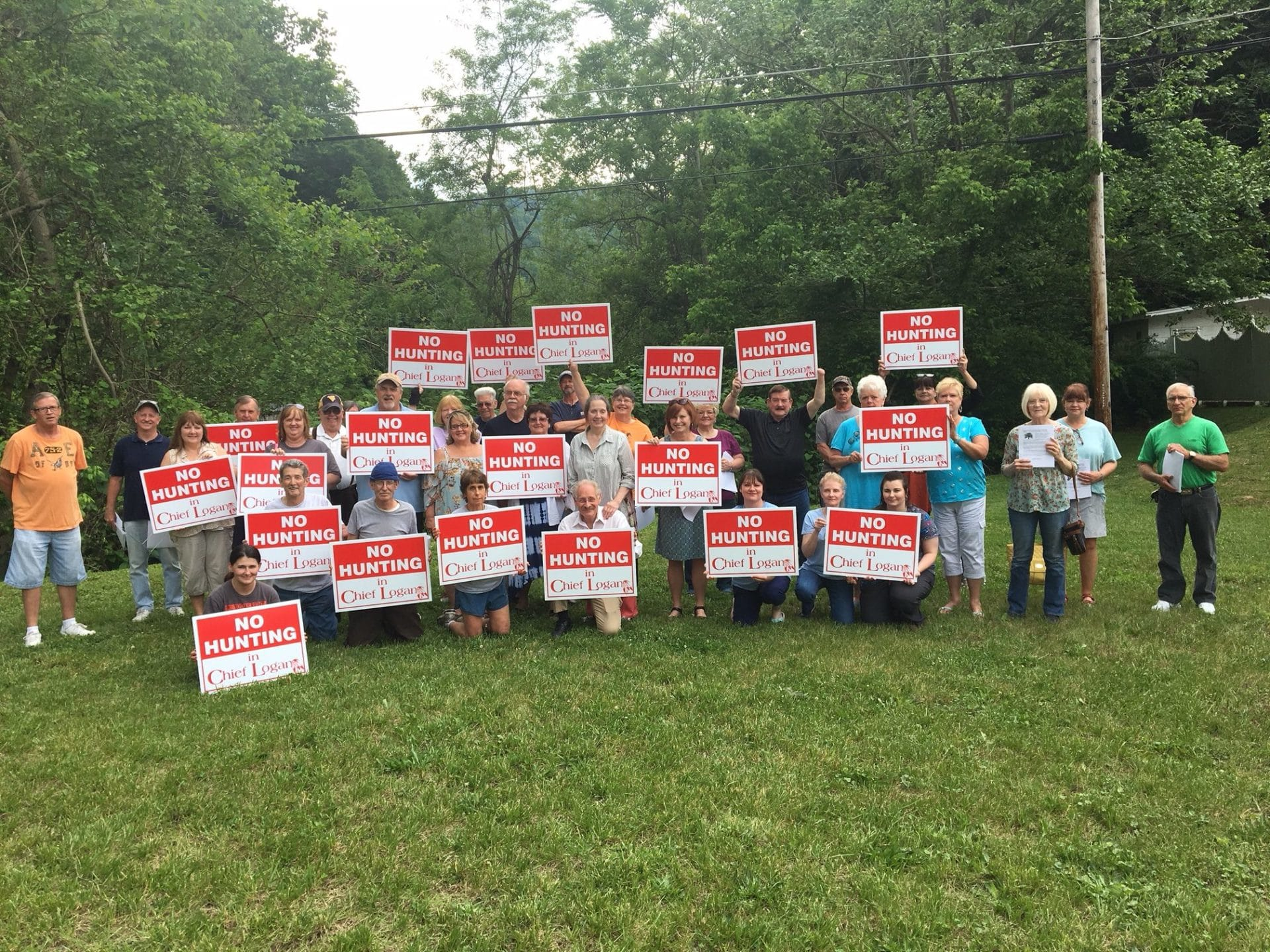 """Large group of protesters holding signs that say """"No Hunting in Chief Logan State Park"""""""
