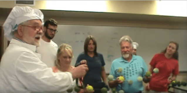 teacher in chef's hat demonstrates climate science activity